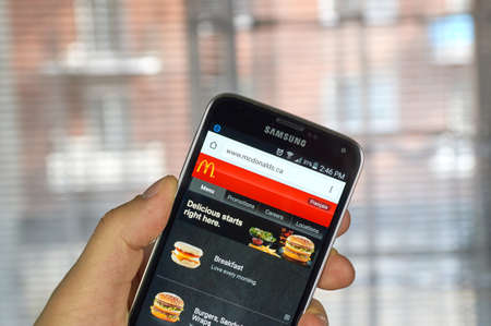 MONTREAL, CANADA - MARCH 20, 2016 - McDonald's  site on Samsung S5's screen. McDonald's is the world's largest chain of hamburger fast food restaurants.