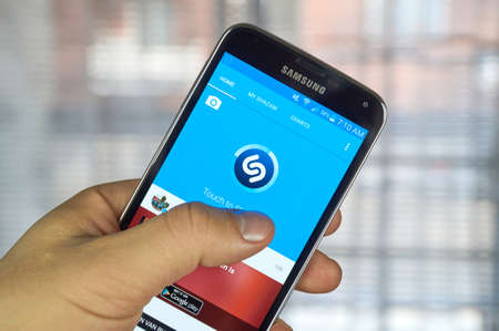 figure out: MONTREAL, CANADA - MARCH 20, 2016 - Shazam mobile application on Samsung S5s screen. Shazam is a free application that helps users figure out the name of a catchy song.