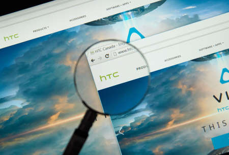 htc: MONTREAL, CANADA - MARCH 25, 2016 - HTC internet page under magnifying glass. HTC Corporation is a Taiwanese multinational manufacturer of smartphones and tablets.