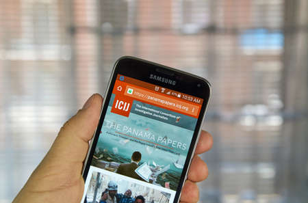 investigative: MONTREAL, CANADA - APRIL 5, 2016 : ICIJ web page on mobile phone. ICIJ is International Consortium of Investigative Journalists and well known for The Panama Papers.