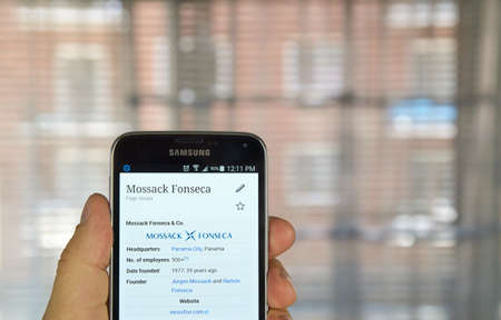 wikipedia: MONTREAL, CANADA - APRIL 5, 2016 : Mossack Fonseca page on Wikipedia on mobile phone. Mossack Fonseca is a Panamanian law firm well known for the biggest leak in the history called The Panama Papers.