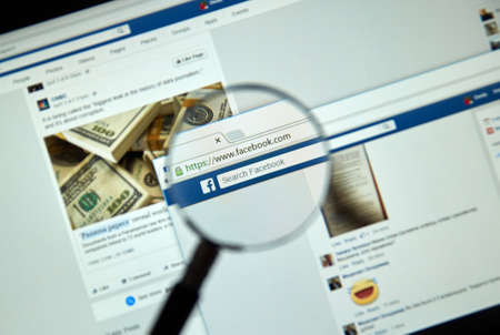 MONTREAL, CANADA - MARCH 25, 2016 - Facebook page under magnifying glass. Facebook is a corporation and online social networking service.