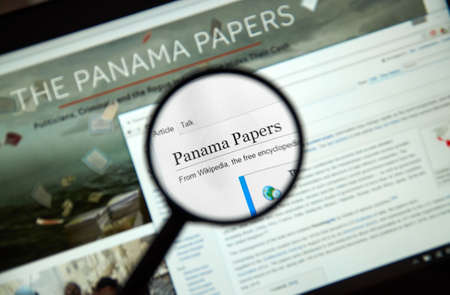 secret: MONTREAL, CANADA - APRIL 5, 2016 : The Panama Papers web page under magnifying glass. Its a leaked set of 11.5 million confidential documents.