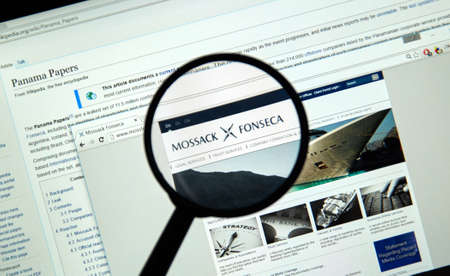 investigative: MONTREAL, CANADA - APRIL 5, 2016 : Mossack Fonseca page under magnifying glass. Mossack Fonseca is a Panamanian law firm well known for the biggest leak in the history called The Panama Papers.