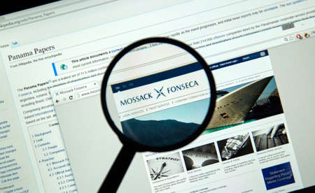 MONTREAL, CANADA - APRIL 5, 2016 : Mossack Fonseca page under magnifying glass. Mossack Fonseca is a Panamanian law firm well known for the biggest leak in the history called The Panama Papers. Sajtókép