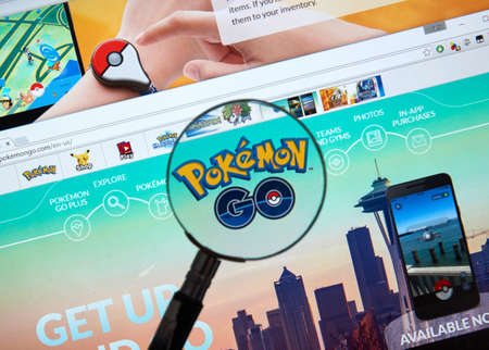 reality: MONTREAL, CANADA - JULY, 14 : Pokemon Go home page under magnifying glass. Pokemon Go, a free-to-play augmented reality mobile game developed by Niantic for iOS and Android devices.