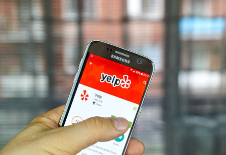 samsung: MONTREAL, CANADA - August 8, 2016 - Yelp mobile app on screen of Samsung S7 in hand. Yelp is a crowd-sourced local business review and social networking site and company.