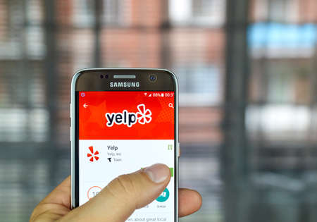 MONTREAL, CANADA - August 8, 2016 - Yelp mobile app on screen of Samsung S7 in hand. Yelp is a crowd-sourced local business review and social networking site and company.