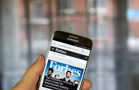 reviews: MONTREAL, CANADA - MARCH 10, 2017 : Forbes on Samsung S7. Forbes is an American business magazine. It features original articles on finance, industry, investing, and marketing topics. Editorial