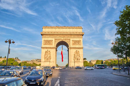 champs elysees: PARIS, FRANCE - MAY 10, 2017 : Arc de Triomphe with french flag in the evening. Triumphal Arch is one of the most famous monuments in Paris, standing at the center of Place Charles de Gaull