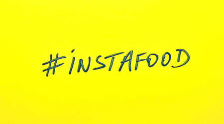 Popular hashtag instafood written on a yellow paper Stock Photo