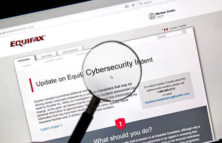 MONTREAL, CANADA - SEPTEMBER, 25 : Equifax Canada home page with information about cybersecurity incident under magnifying glass. Equifax Inc. is a consumer credit reporting agency. Selective focus. Sajtókép