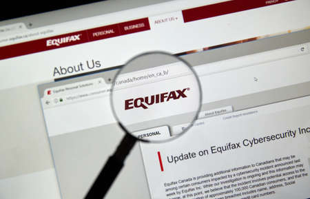MONTREAL, CANADA - SEPTEMBER, 25 : Equifax Canada home page with information about cybersecurity incident under magnifying glass . Equifax Inc. is a consumer credit reporting agency. Selective focus. Editorial