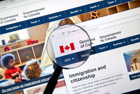 MONTREAL, CANADA - NOVEMBER 17, 2017: Official web page of Canadian Government under magnifying glass where every user can find information about Canadian Government and its Departments and services.