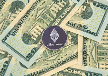 MONTREAL, CANADA - MARCH 10, 2018: Ethereum cryptocurrency silver coin and logo on american dollar bank notes. Publikacyjne