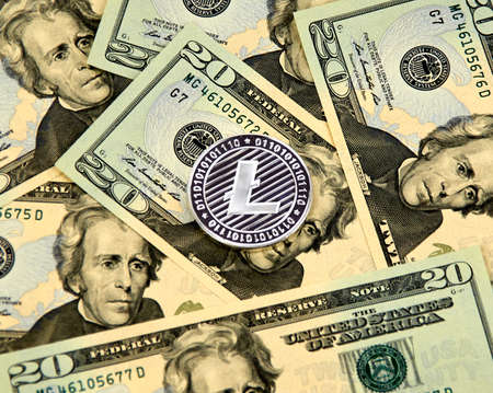 MONTREAL, CANADA - MARCH 10, 2018: Litecoin cryptocurrency silver coin and logo on american dollar bank notes. Publikacyjne