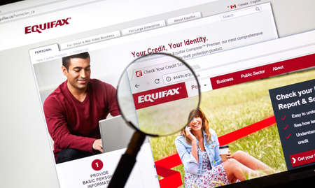 MONTREAL, CANADA - APRIL 10, 2018 : Equifax official site and logo under magnifying glass. Equifax Inc. is a consumer credit reporting agency.