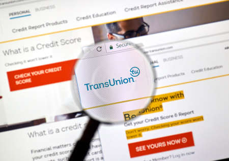 MONTREAL, CANADA - MARCH 10, 2018: Transunion web site under magnifying glass. TransUnion is a consumer credit reporting agency, it collects information on over one billion individual consumers.