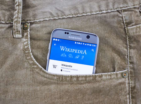 MONTREAL, CANADA - OCTOBER 10, 2017: Wikipedia mobile application on a cellphone screen in a jeans pocket. Wikipedia is a multilingual free encyclopedia based on a model of openly editable content Publikacyjne