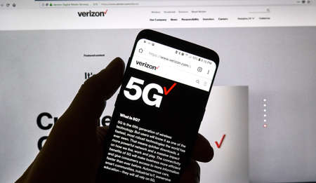 MONTREAL, CANADA - SEPTEMBER 13, 2018: A hand holding a cellphone with opened Verizon 5g official web page. Verizon Wireless is an American telecommunications company which offers wireless products Editorial