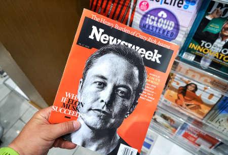 MIAMI, USA - 23. AUGUST 2018: Newsweek-Magazin mit Elon Musk auf Hauptseite in einer Hand. Newsweek ist ein in den USA bekanntes und beliebtes Wochenmagazin