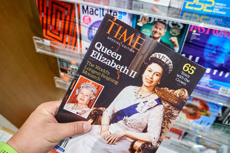 MIAMI, USA - AUGUST 23, 2018: Time magazine with Queen Elizabeth II on the cover in a hand. Time is an American weekly news magazine Editorial