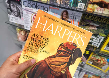 MIAMI, USA - AUGUST 22, 2018: Harpers magazine in a hand over a stack of magazines. Harpers Magazine is a popular monthly magazine of literature, culture, finance and arts