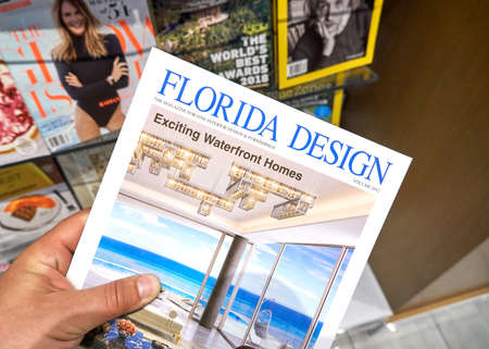 MIAMI, USA - AUGUST 22, 2018: Florida Design magazine in a hand over a stack of magazines. 新聞圖片