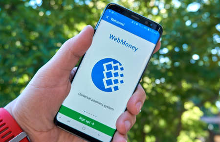 MONTREAL, CANADA - August 28, 2018: Webmoney android app on Samsung s8 screen in a hand.