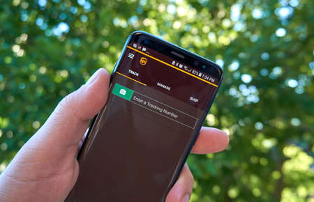 MONTREAL, CANADA - August 28, 2018: UPS tracking android app on Samsung s8 screen in a hand.