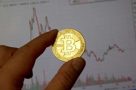 MONTREAL, CANADA - SEPTEMBER 8, 2018: A hand holding Bitcoin gold crypto currency coin in a hand over a bitcoin chart on a desktop screen. Publikacyjne