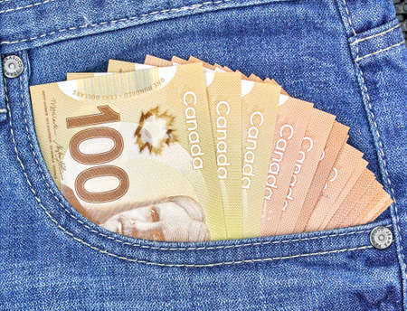 canadian money in a pocket of a blue jeans