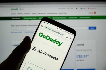 MONTREAL, CANADA - OCTOBER 3, 2018 : GoDaddy page, logo and app on a S8 Samsung cell phone. GoDaddy is an American publicly traded Internet domain registrar company. Редакционное