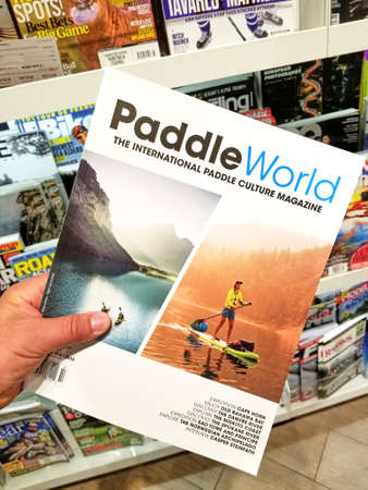 TORONTO, CANADA - DECEMBER 9, 2018: Paddle World magazine in a hand over a stack of magazines. Paddle World Magazine is an international all paddlesports magazine.