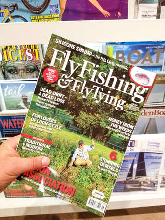 TORONTO, CANADA - DECEMBER 9, 2018: Fly Fishing and Fly Tying magazine in a hand over a stack of magazines.