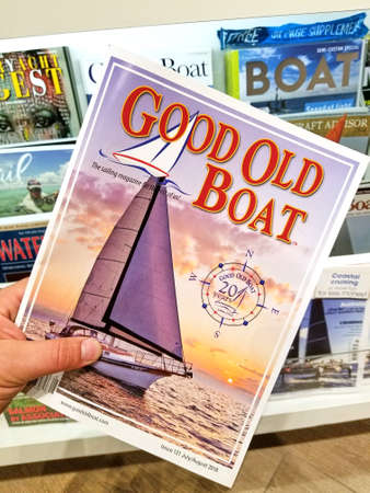 TORONTO, CANADA - DECEMBER 9, 2018: Good Old Boat magazine in a hand over a stack of magazines. Good Old Boat is a niche magazine dedicated to hands-on sailboat enthusiasts and owners Banque d'images - 115643018