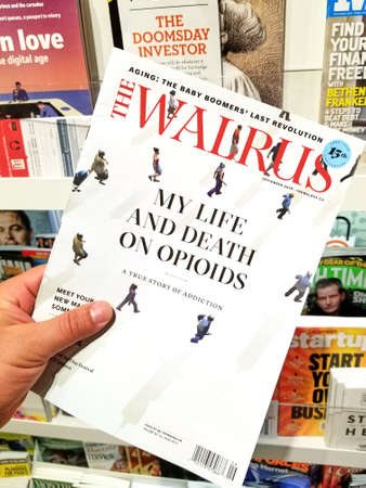 TORONTO, CANADA - DECEMBER 9, 2018: The Walrus magazine in a hand over a stack of magazines. The Walrus is a Canadian general interest magazine 新聞圖片