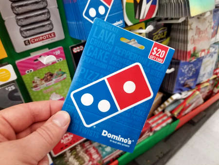 PLATTSBURGH, USA - JANUARY 21, 2019 : Dominos Pizza gift card in a hand over a shelves with different giftcards in a Walmart store.
