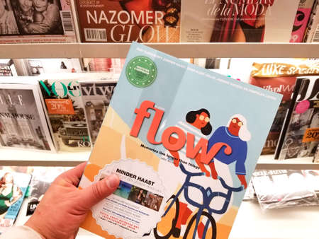 AMSTERDAM, NETHERLANDS: - OCTOBER 8, 2018: Flow magazine in a hand over a stack of magazines.
