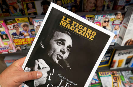 MONTREAL, CANADA - OCTOBER 9, 2018: Le Figaro magazine in a hand with Charles Aznavour on the front cover over a stack of magazines. Le Figaro magazine is a French language weekly news magazine