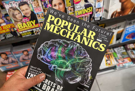 MONTREAL, CANADA - OCTOBER 9, 2018: Popular Mechanics magazine in a hand over a stack of magazines. Popular Mechanics is a magazine of popular science, technology, automotive, home and electronics.