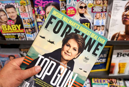 MONTREAL, CANADA - OCTOBER 9, 2018: Fortune magazine in a hand over a stack of magazines with Marillyn Hewson on the cover. Fortune is an American business magazine.