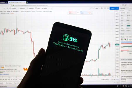 MONTREAL, CANADA - APRIL 26, 2019: BW.com cryptocurrency exchange logo and application on Android Samsung Galaxy s9 Plus screen in a hand over a laptop display with bitcoin chart on it. Editorial