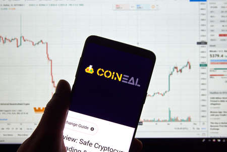 MONTREAL, CANADA - APRIL 26, 2019: Coineal cryptocurrency exchange logo and application on Android Samsung Galaxy s9 Plus screen in a hand over a laptop display with bitcoin chart on it. Editorial