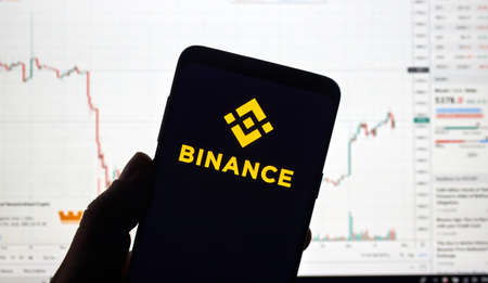 MONTREAL, CANADA - APRIL 26, 2019: Binance cryptocurrency exchange logo and application on Android Samsung Galaxy s9 Plus screen in a hand over a laptop display with bitcoin chart on it. Editorial