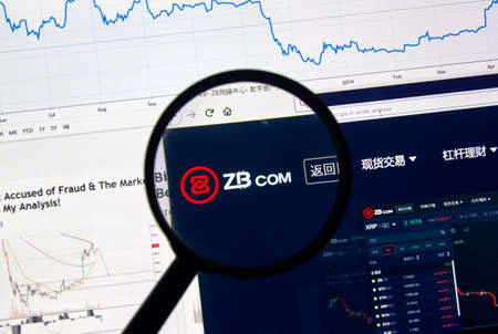 MONTREAL, CANADA - APRIL 26, 2019: ZB.com cryptocurrency digital assets exchange logo and home page on a laptop screen under magnifying glass. Editorial