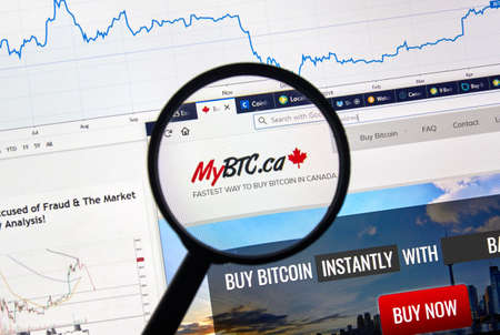 MONTREAL, CANADA - APRIL 26, 2019: MyBTC.ca cryptocurrency digital assets exchange logo and home page on a laptop screen under magnifying glass.
