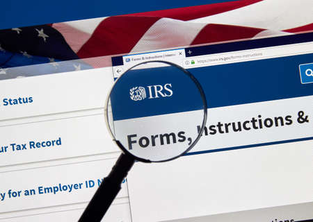 MONTREAL, CANADA - APRIL 24, 2019 : IRS Forms and Instructions USA Government home page under magnifying glass. IRS.com is an official web site of Internal Revenue Service