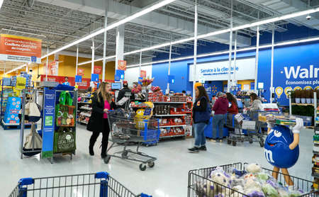 MONTREAL, CANADA - APRIL 30, 2019: People at cashier in Walmart store. Walmart is an American multinational retail corporation which operates a chain of hypermarkets.