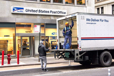 NEW YORK, USA - DECEMBER 14, 2018: USPS postman on a mail delivery truck in New York. USPS is an independent agenc of US federal government responsible for providing postal service in the US. 新聞圖片